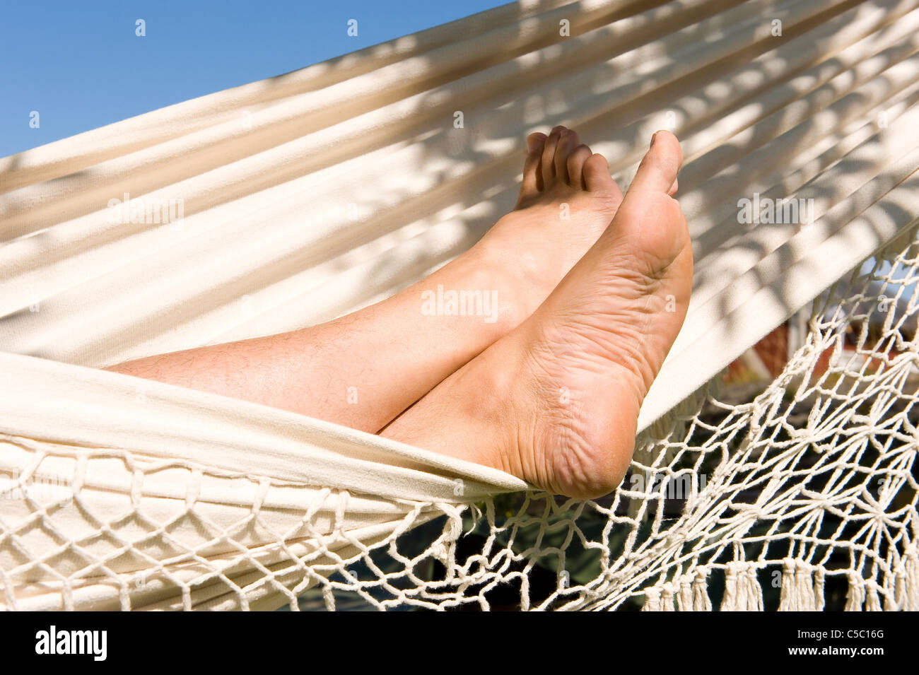 Close-up of bare feet resting in hammock on a sunny day - Stock Image