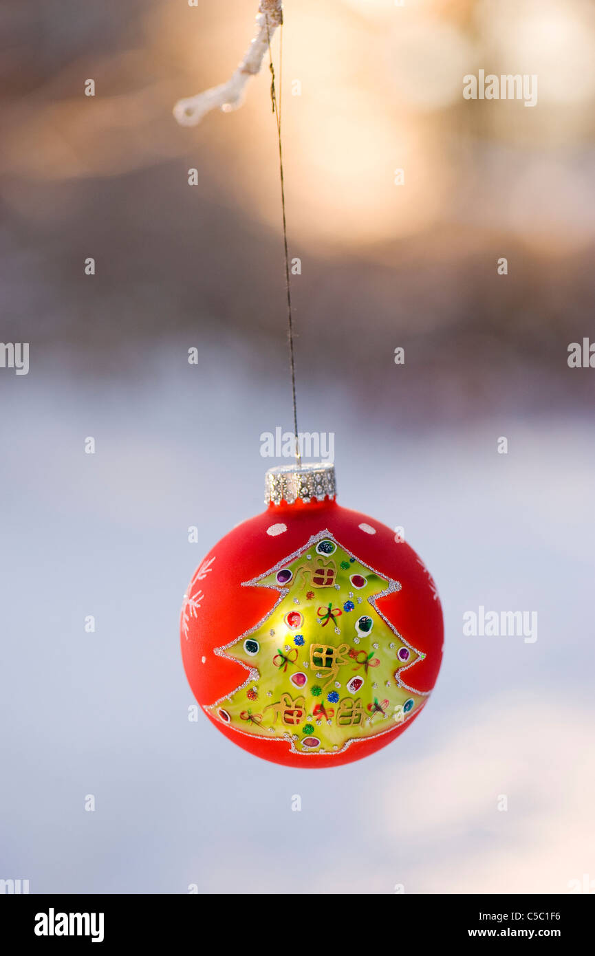 Close-up of golden Christmas tree on red bauble against blurred background - Stock Image