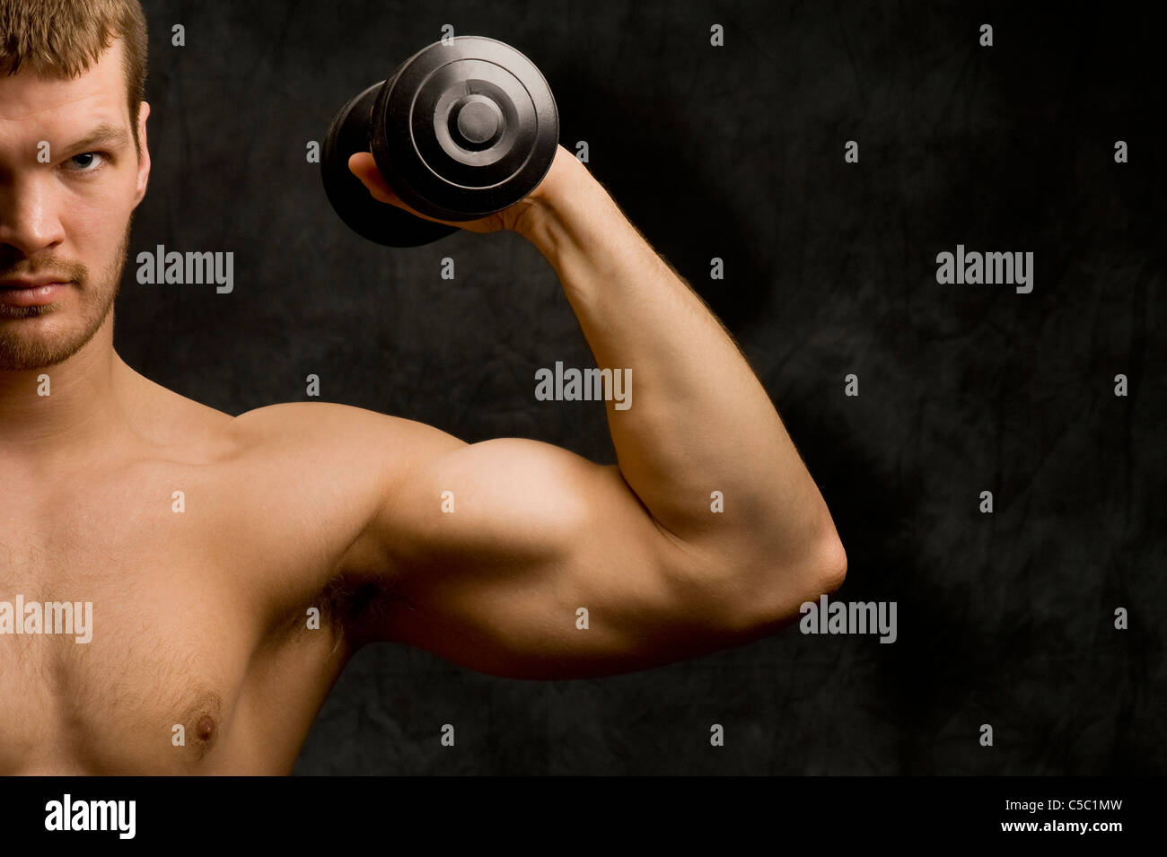 Cropped close-up portrait of macho man with dumbbell over gray background - Stock Image