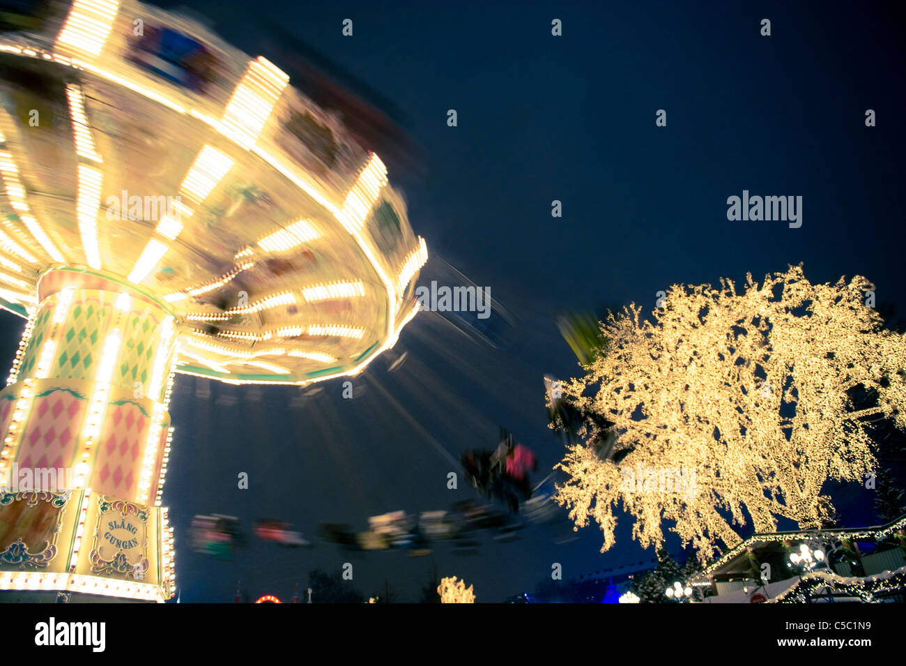 Motion blur of people spinning on illuminated swing ride by lit tree against clear blue sky at night - Stock Image