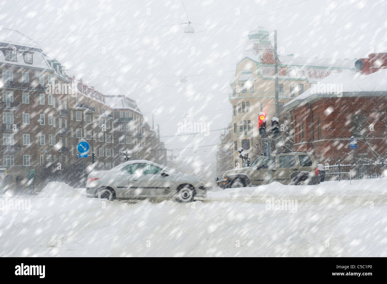 Snow chaos in city traffic against buildings - Stock Image