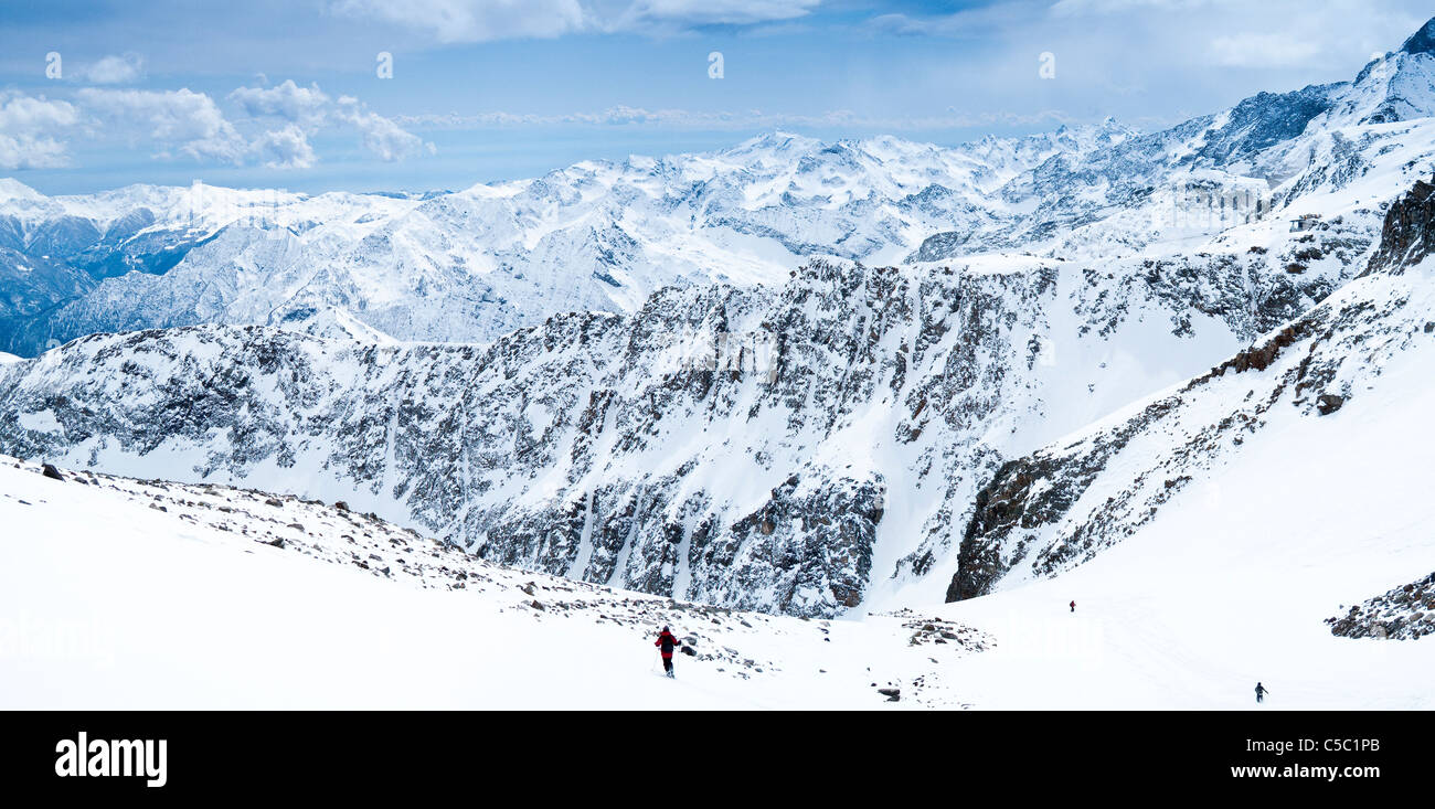 Mid distance of off piste skiing against snowy mountains - Stock Image