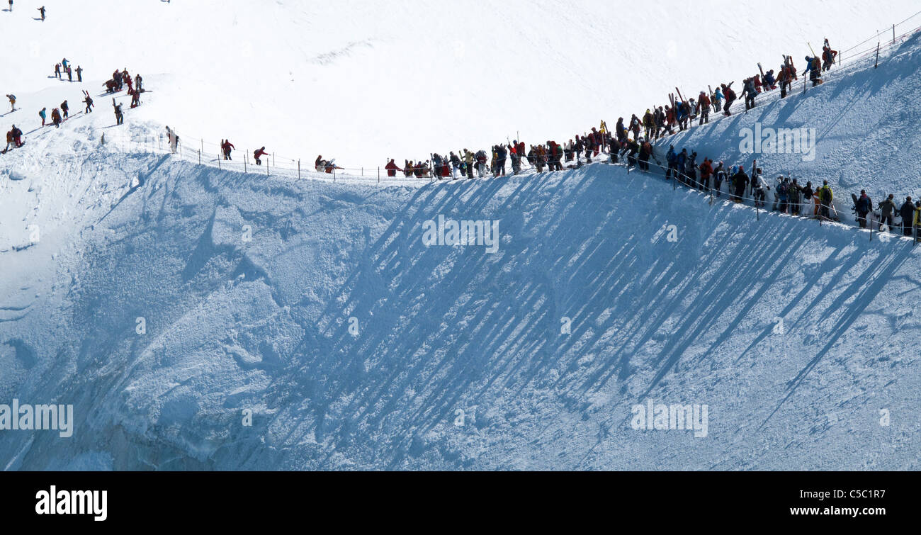Group of people in a row on the alps at Chamonix against sky, France - Stock Image
