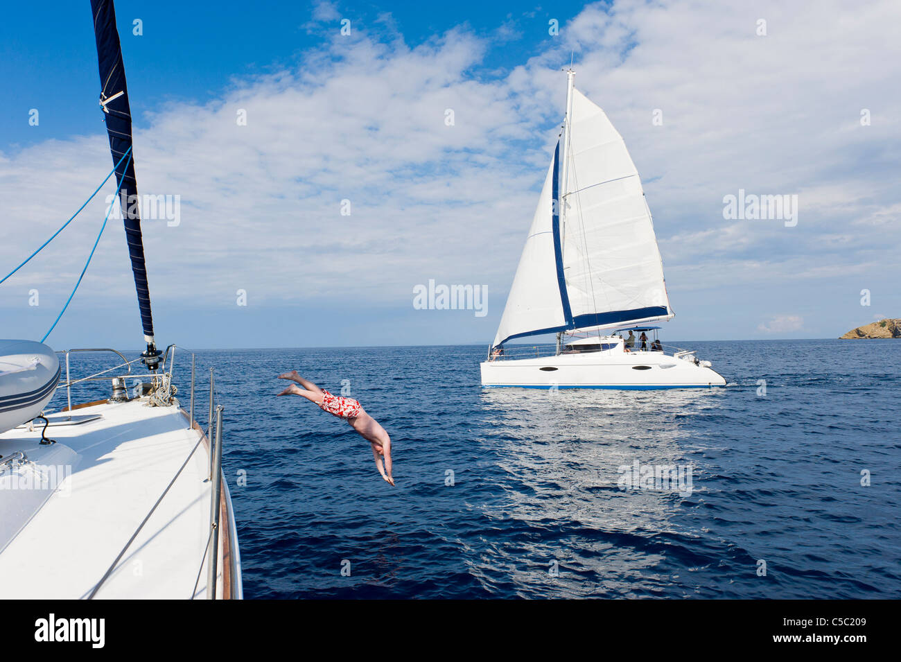 Man jumps into the sea from sailboat with catamaran in the background against cloudy sky - Stock Image