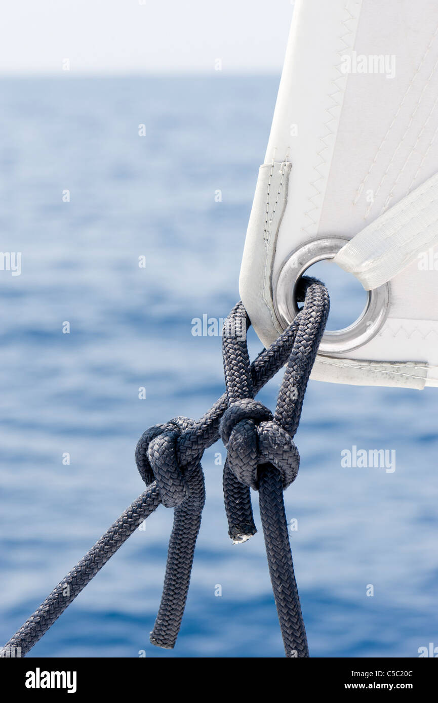 Close-up of sail ship rigging against the water - Stock Image