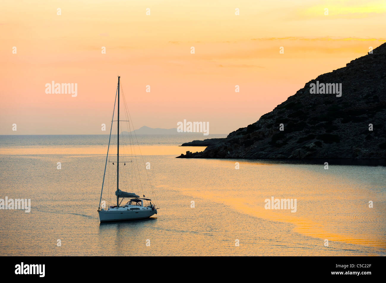 Sailboat anchored in shallow water in the peaceful sea at sunset - Stock Image