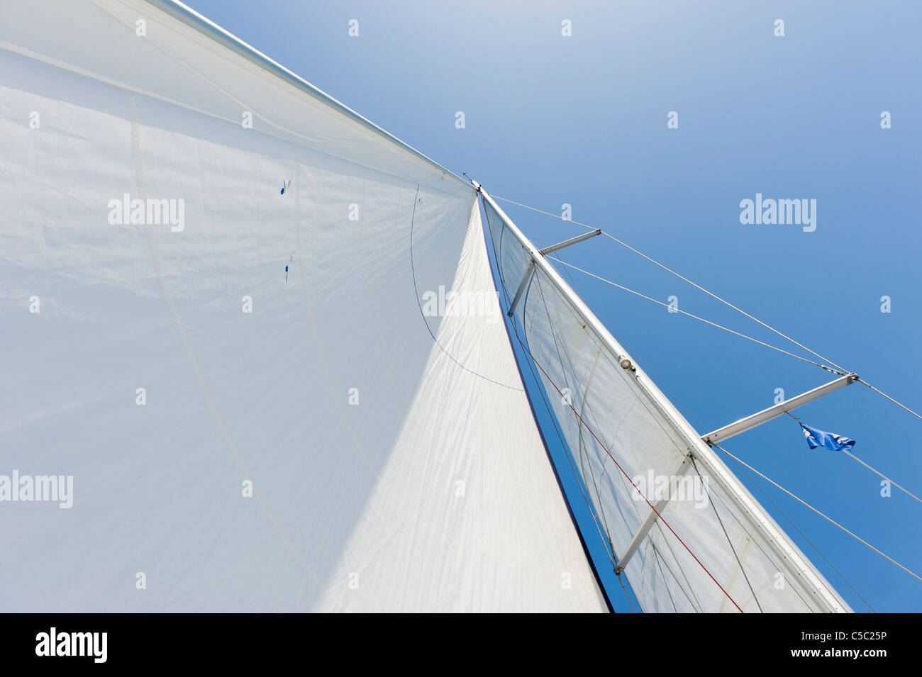 Close-up of a sail bermuda rigged against the blue sky - Stock Image