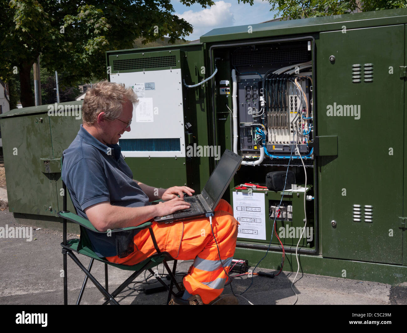 Engineer adding software to Fibre Optics Broadband Network Junction Box. Mossley,Lancashire,England, UK. - Stock Image