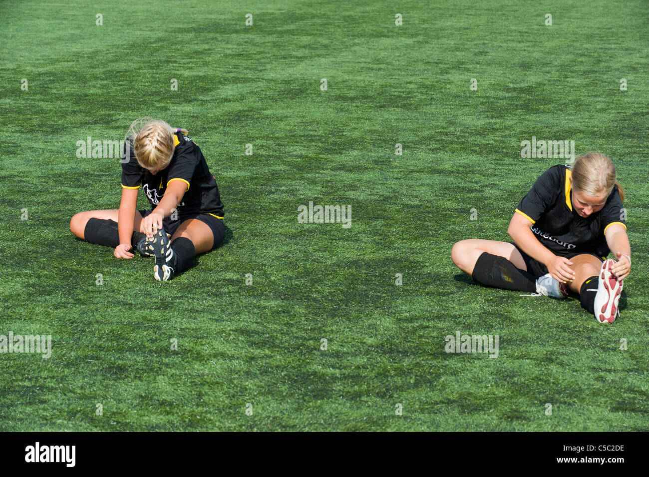 Two girls stretching on the grass at lawn - Stock Image
