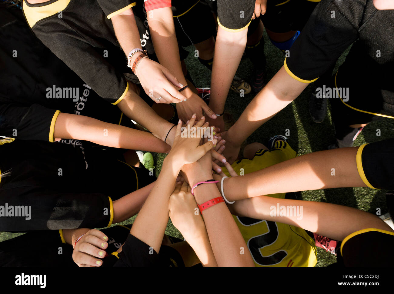 Close-up of football players with hands over one another - Stock Image