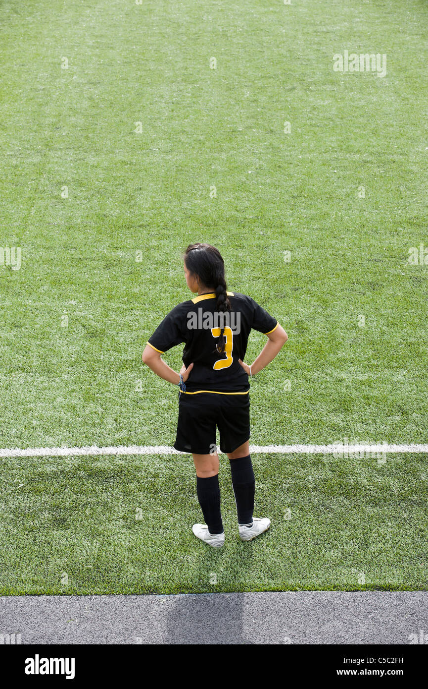 Rear view of a female football substitute standing on grass with hands on hips - Stock Image