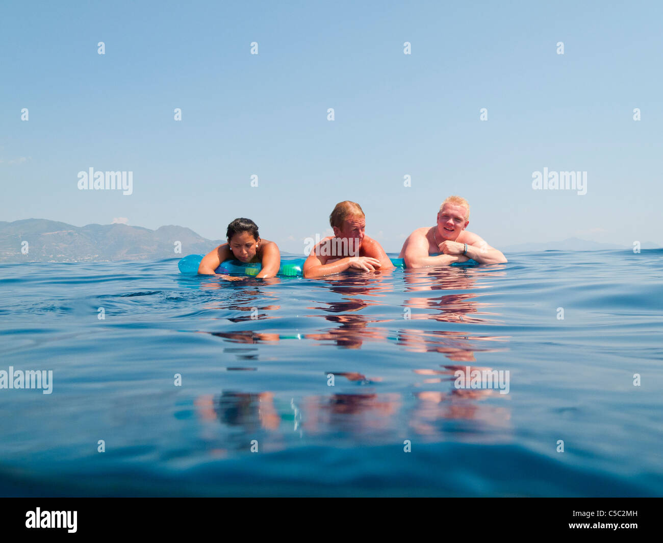 Three people on the air mattresses floating in a row at the sea against clear sky - Stock Image