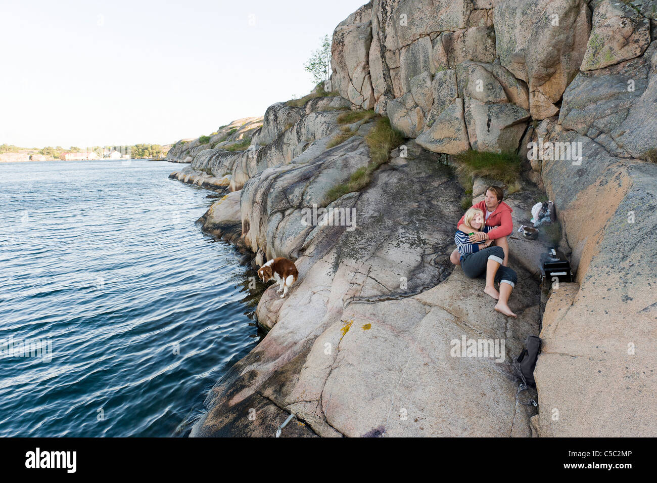 Romantic and relaxed teenage boy and girl on the rock by the peaceful sea - Stock Image