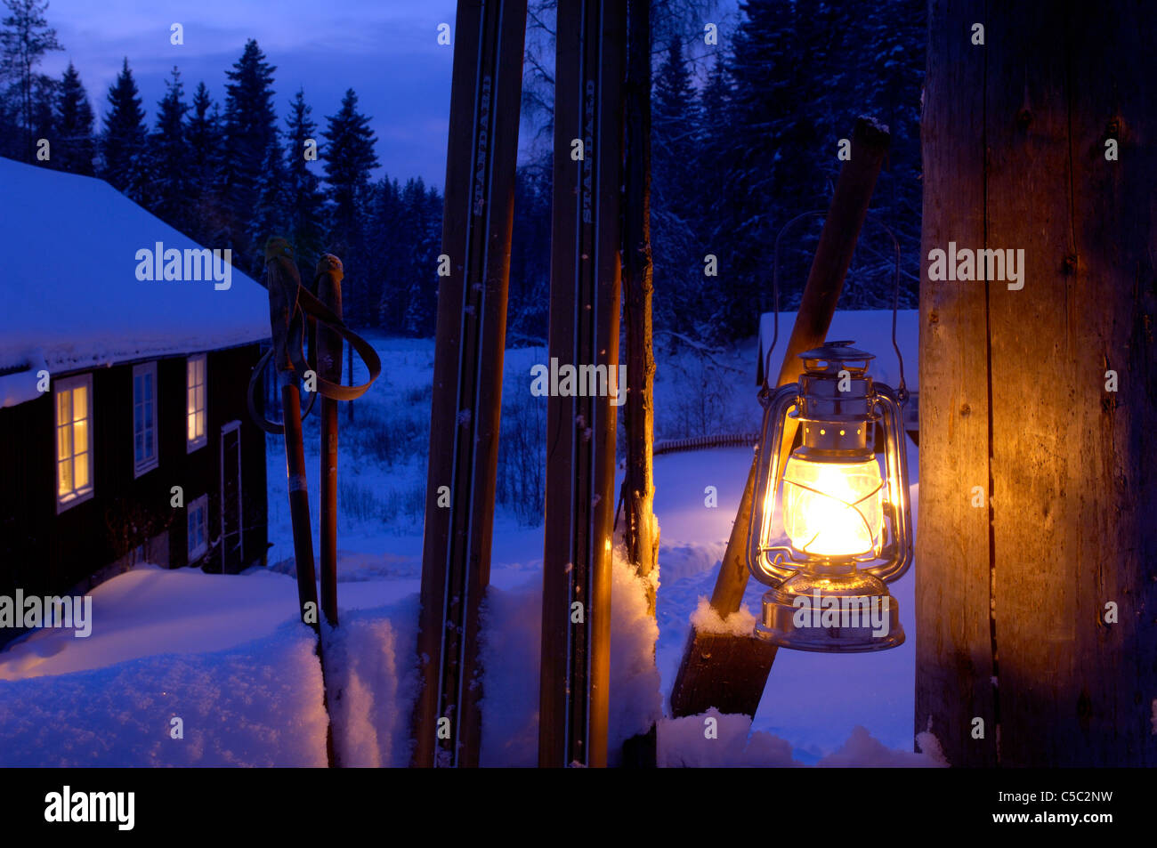 Close-up of lit lantern at the gatepost in the snow - Stock Image