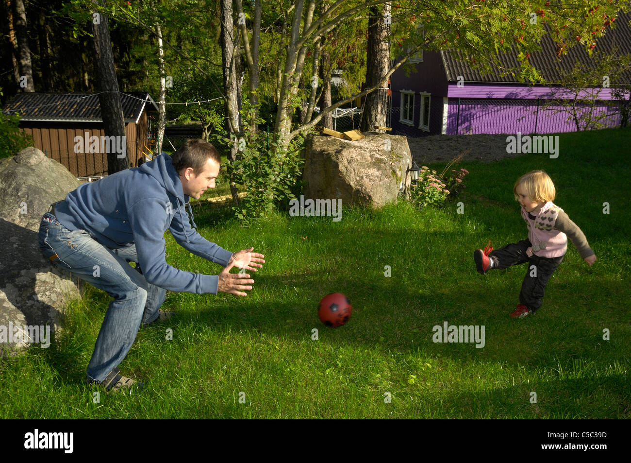 Side view of a man playing soccer with his daughter on the lawn - Stock Image
