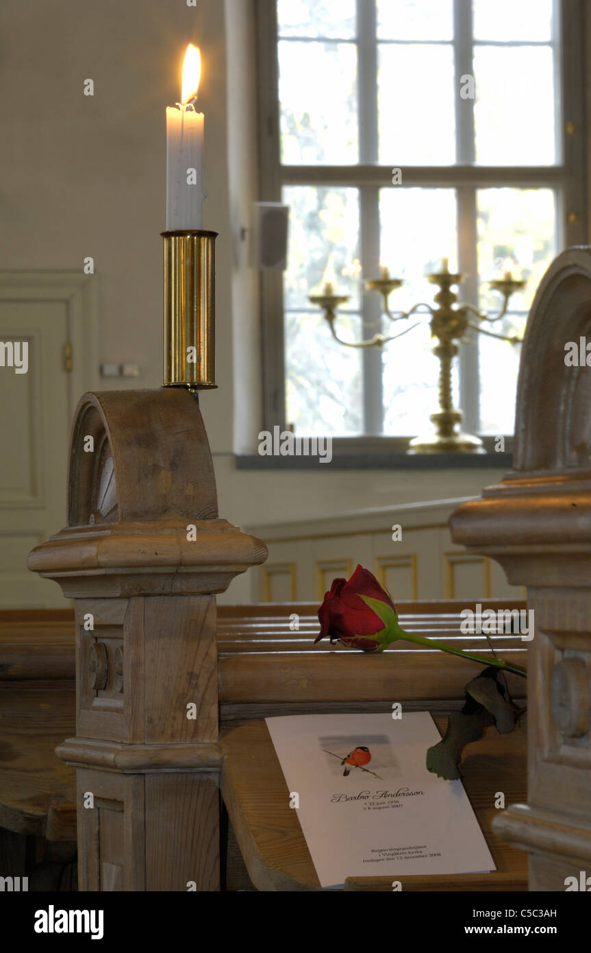 Close-up of a rose and card on pew by lit candle in the church - Stock Image