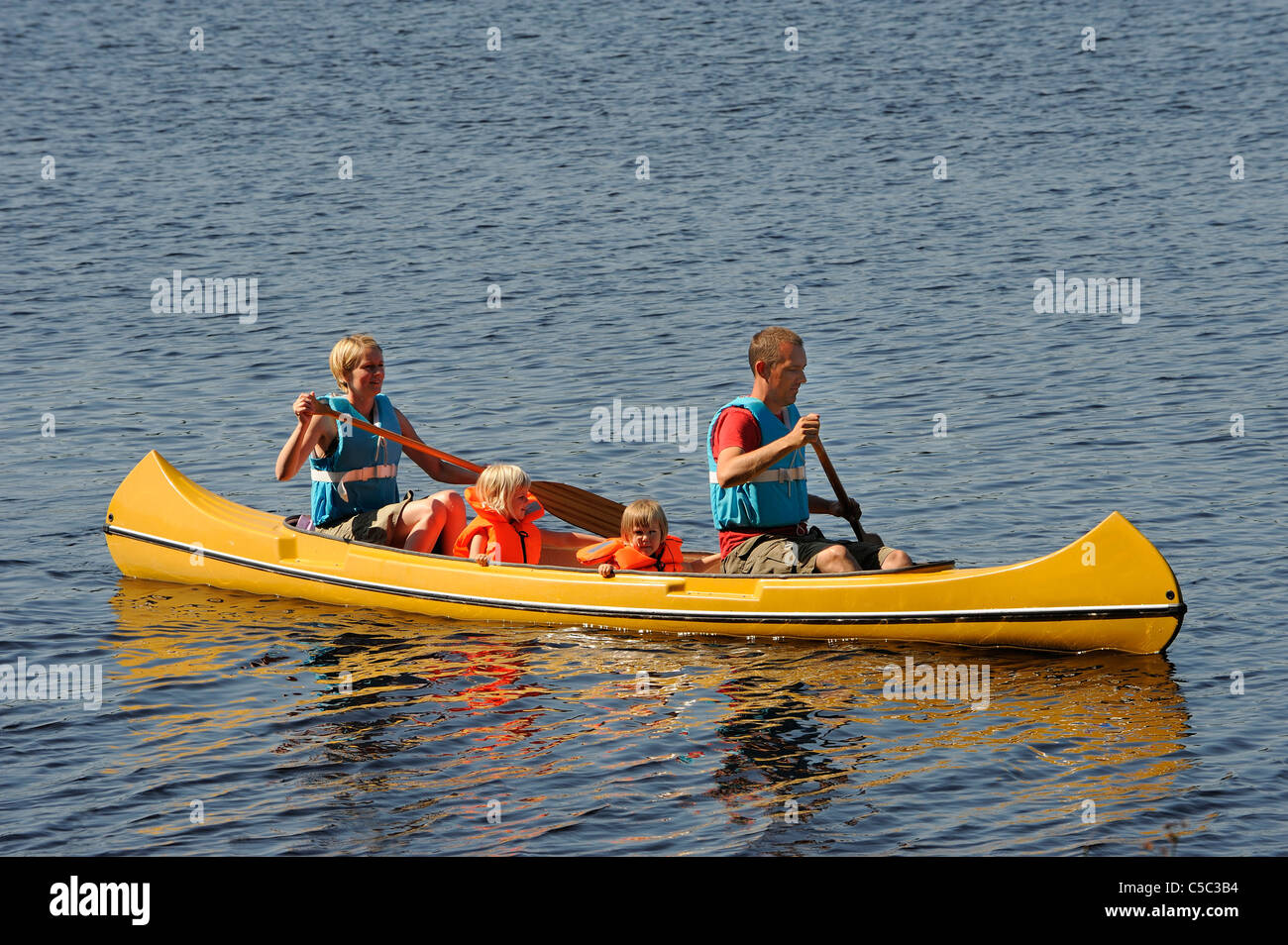 Side View Of A Family Canoeing In Rippled Water