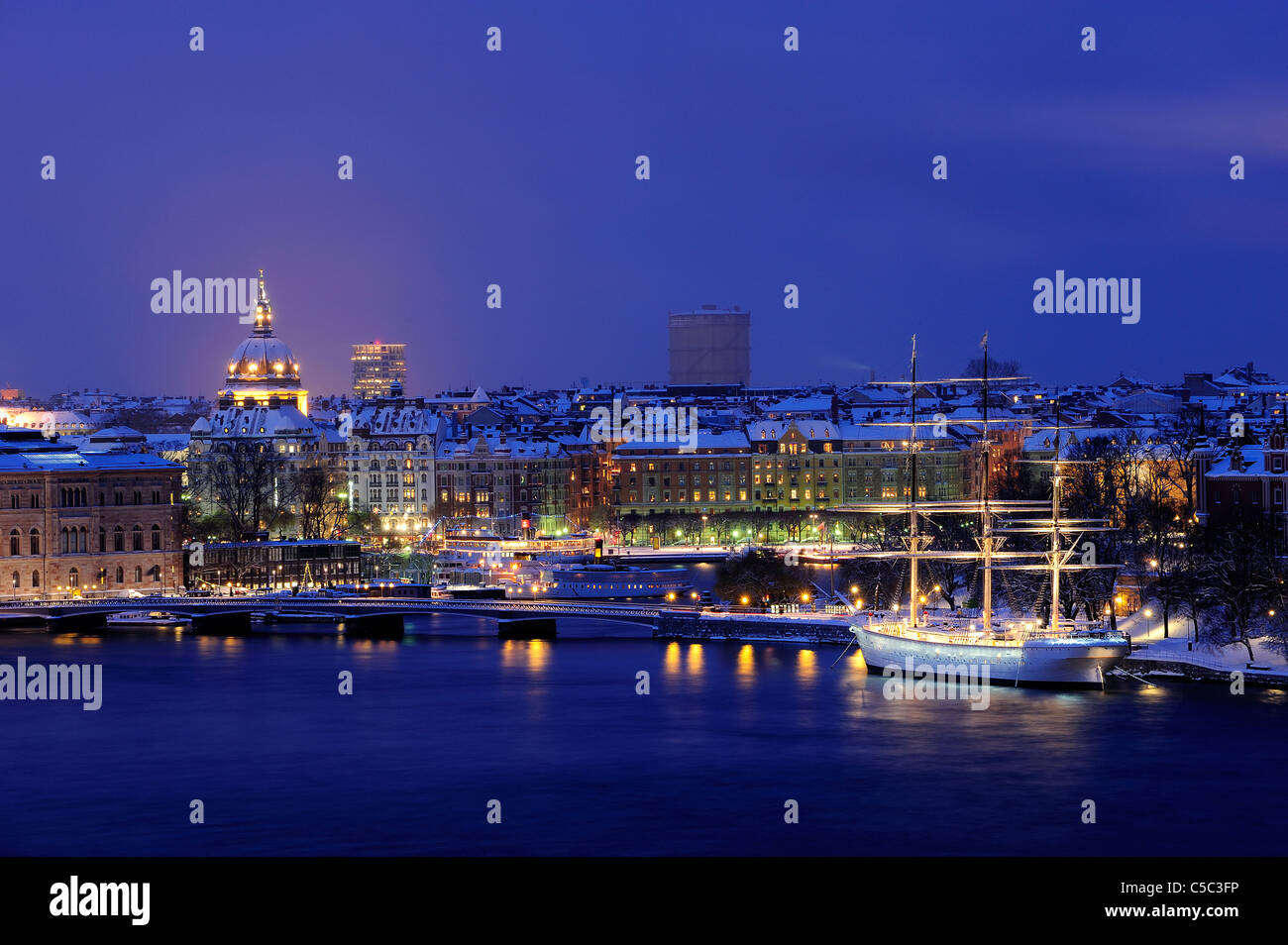Af Chapman with illuminated buildings and placid lake in foreground, Stockholm, Sweden - Stock Image