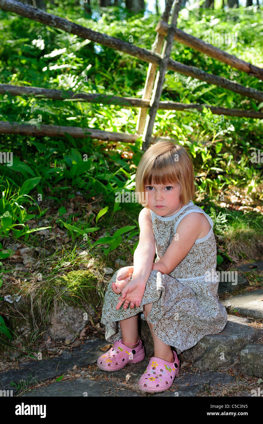 Thoughtful little girl sitting outdoors by fenced plants - Stock Image