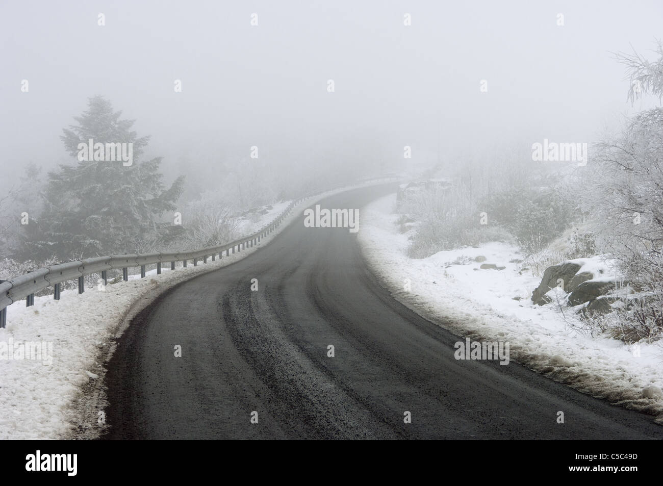 Curvy winter road leading to the mist - Stock Image