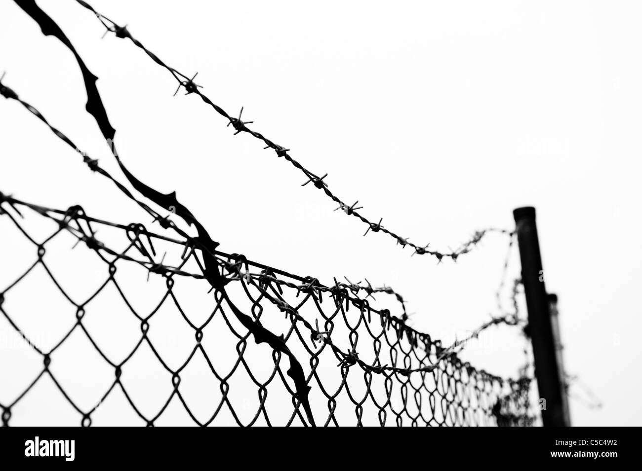 Close-up of barbed wire fence against clear sky - Stock Image