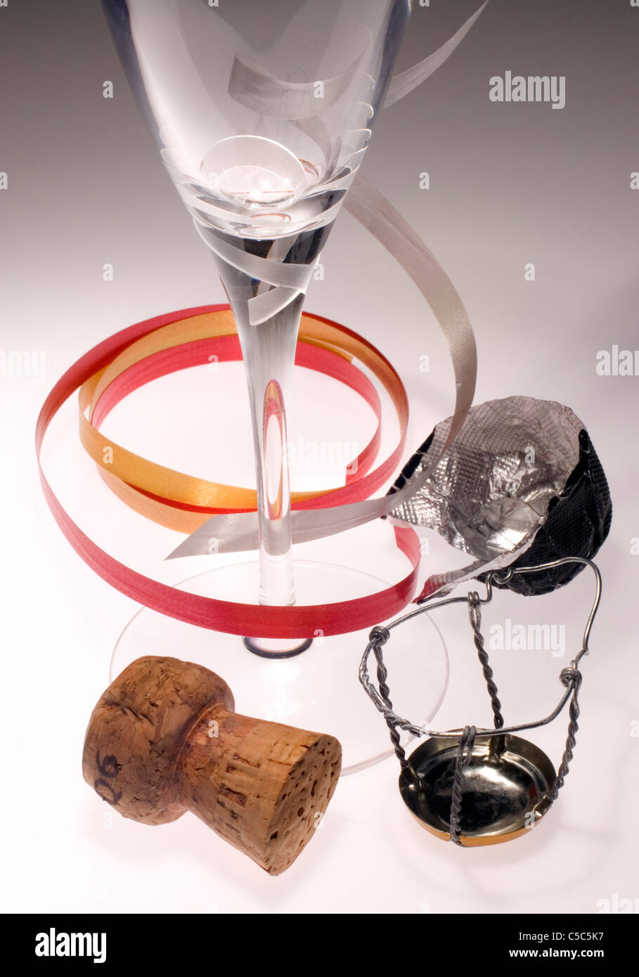 Close-up of champagne flute, cork and seal over white background - Stock Image