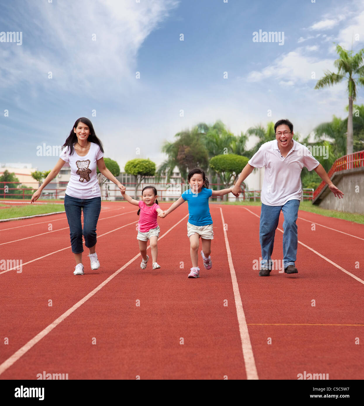 happy asian family running together on the Stadium track Stock Photo