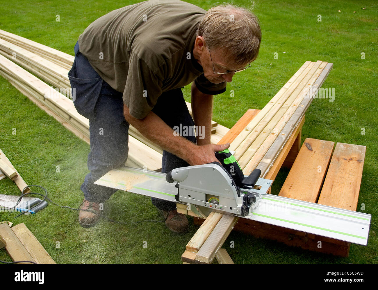 Male joiner using the buzz saw on wood - Stock Image