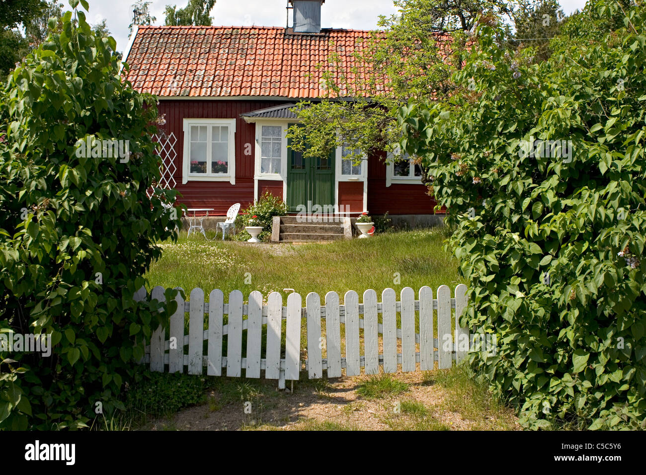 Countryside cottage with white fence and trees - Stock Image