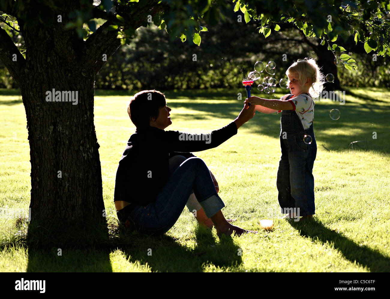 Side view of a little girl and woman playing with soap bubbles in the garden - Stock Image