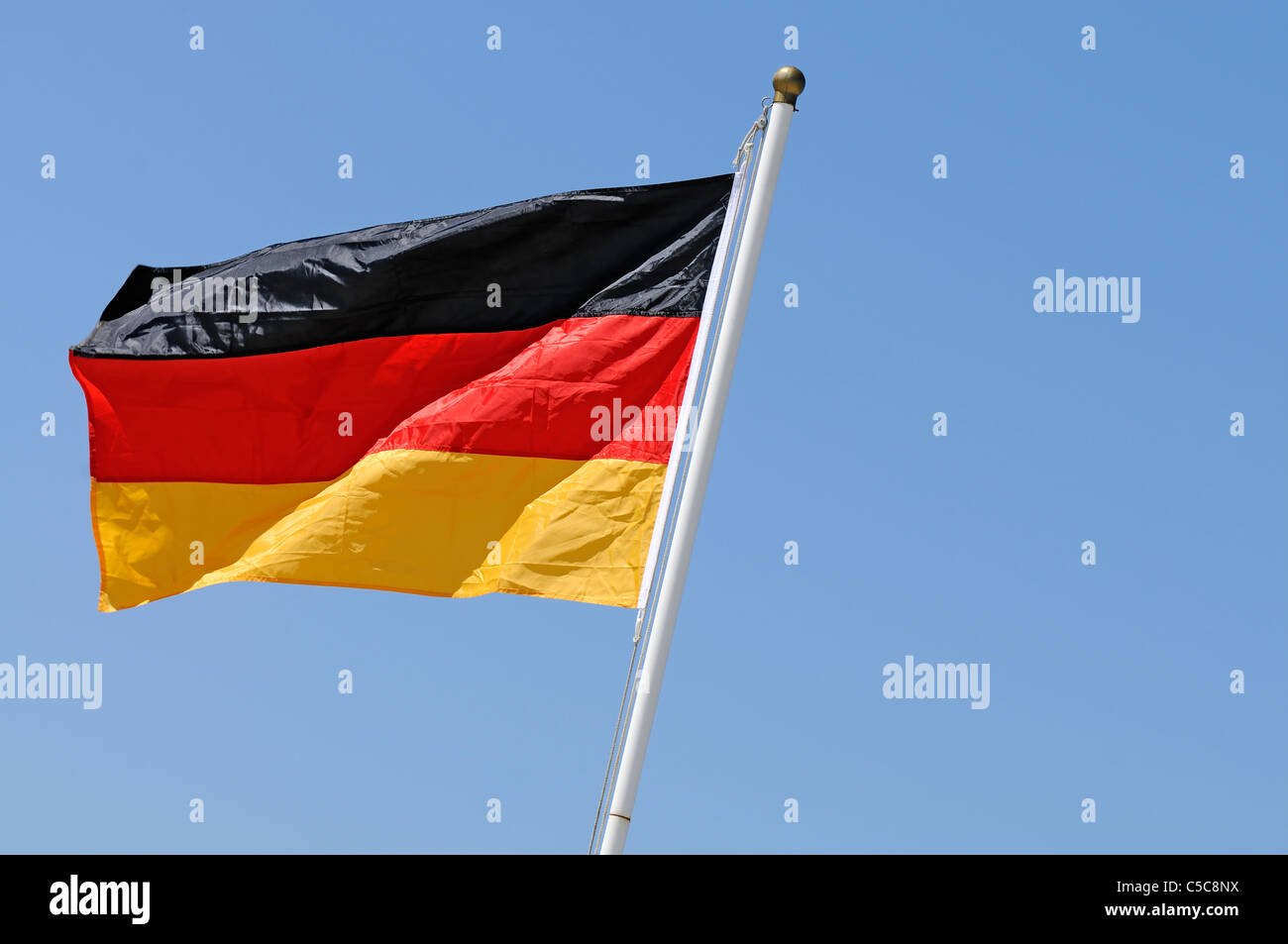 German flag in the wind on blue sky background - Stock Image