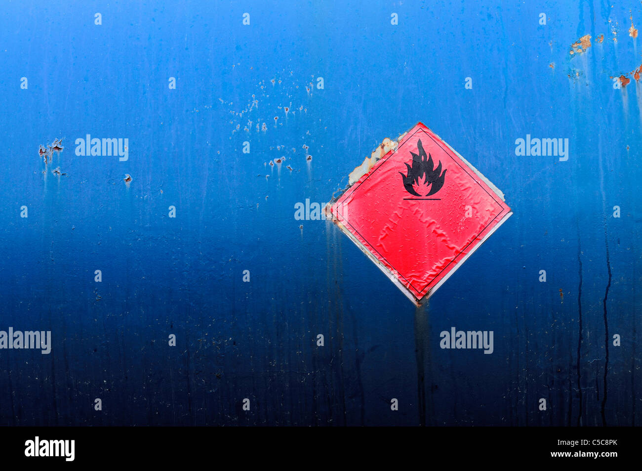 A weathered flammable symbol on grunge blue painted metal background. - Stock Image