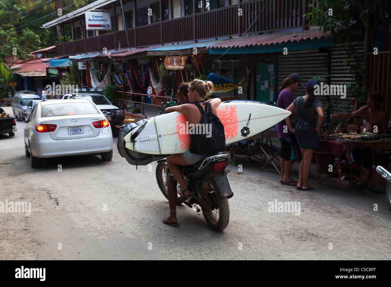 Streetscene with surfers on motorbike wih boards Montezuma Costa Rica - Stock Image
