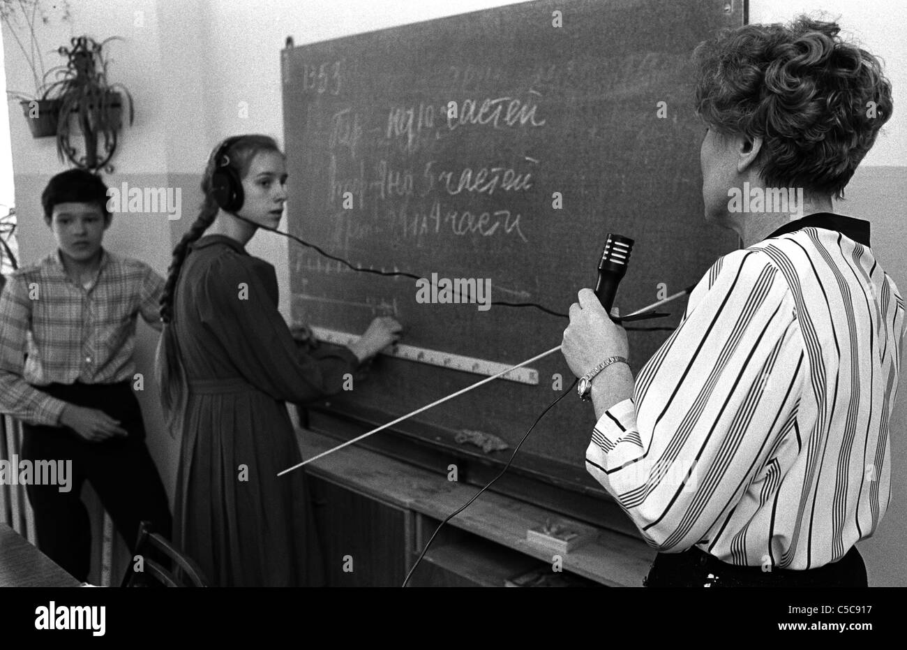 A female teacher in the classroom teaching, with the aid of a microphone and headphones - Stock Image