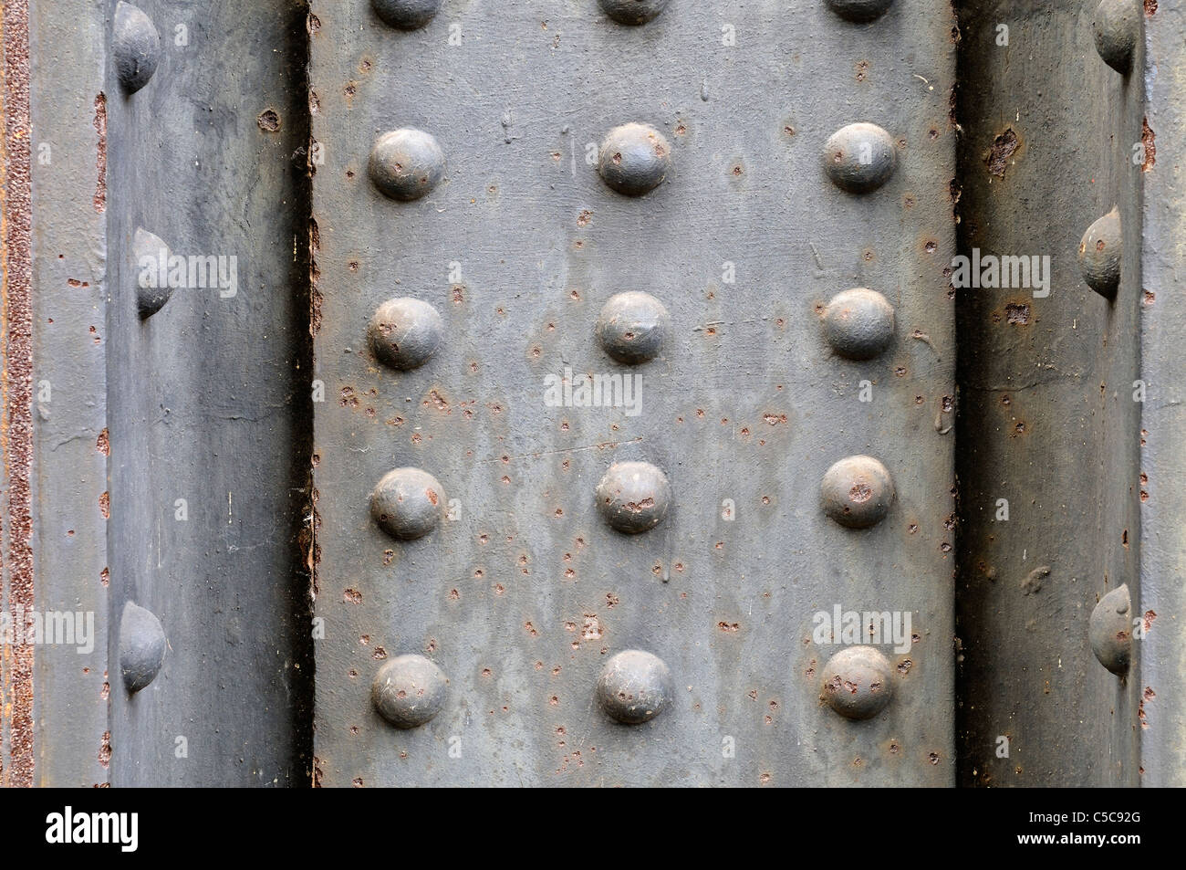 Grungy metal plate background with rivets. - Stock Image