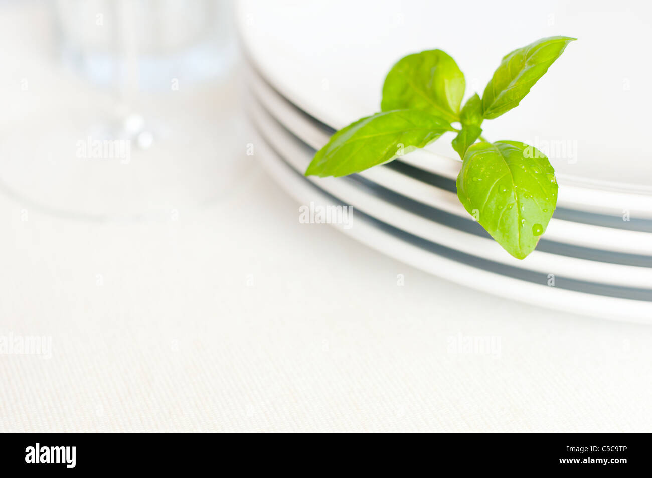 Empty White Plates With Basil Leaf and Wine Glass - Stock Image