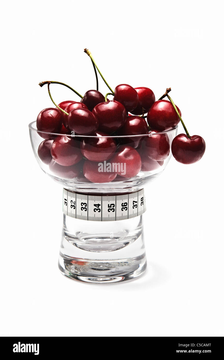Red Cherries in Glass Dish with Tape Measure - Stock Image