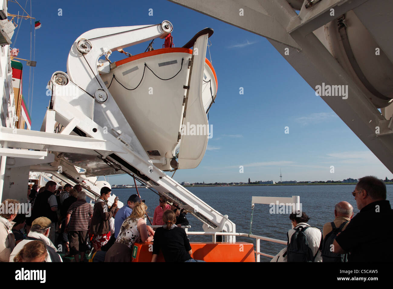 people and life boat on ferry Atlantis; MS Atlantis crossing between Cuxhaven and Heligoland  (Helgoland), Germany - Stock Image