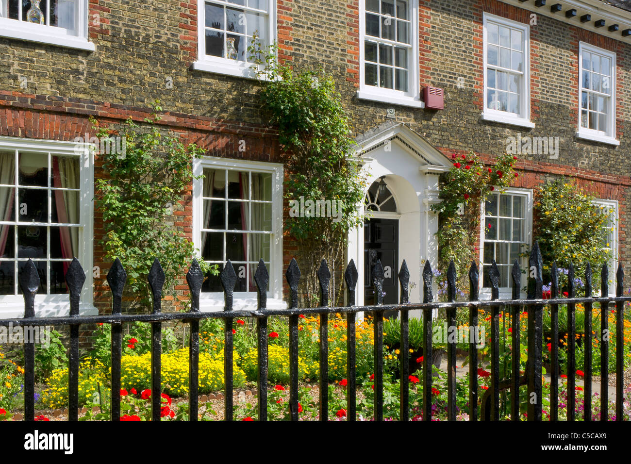 An old house with floral summer border on Palace Green by the Cathedral in Ely, Cambs - Stock Image