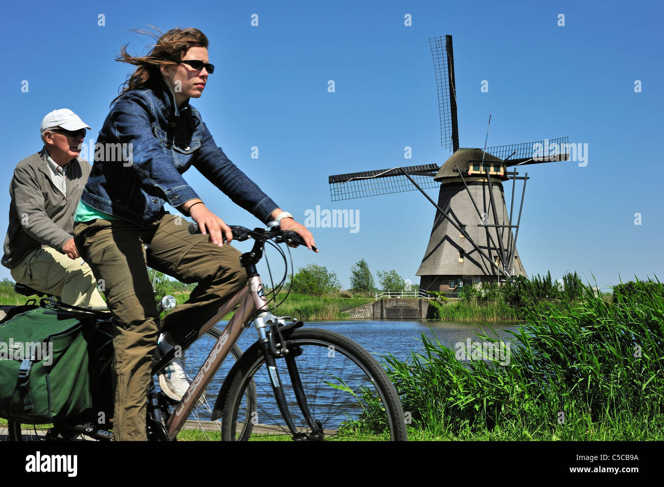 Cyclists riding bikes and thatched windmill at Kinderdijk, a UNESCO World Heritage Site at South Holland, the Netherlands - Stock Image