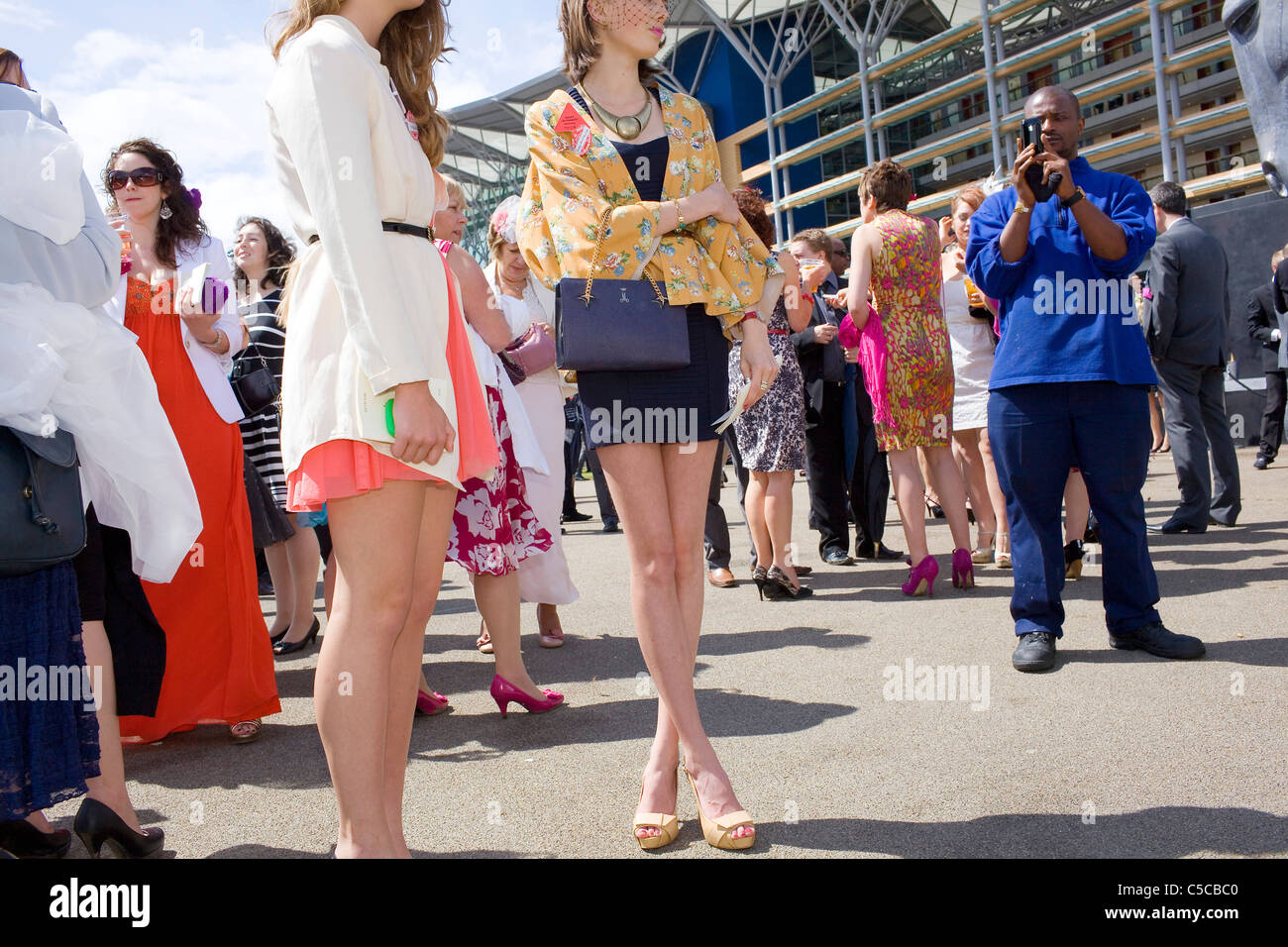 Two women in the crowd at Royal Ascot races are filmed by a black mad with his mobile phone. - Stock Image