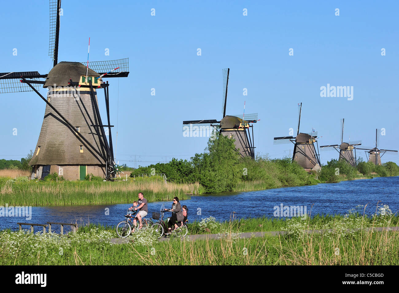 Row of thatched polder windmills along canal at Kinderdijk, a UNESCO World Heritage Site at South Holland, the Netherlands - Stock Image