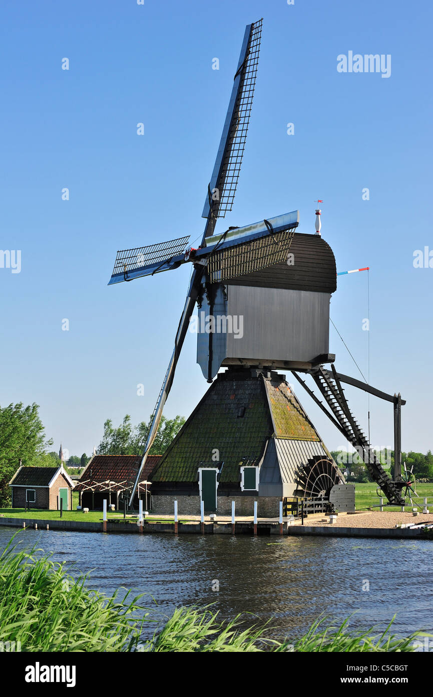 Wooden hollow post windmill along canal at Kinderdijk, a UNESCO World Heritage Site at South Holland, the Netherlands - Stock Image