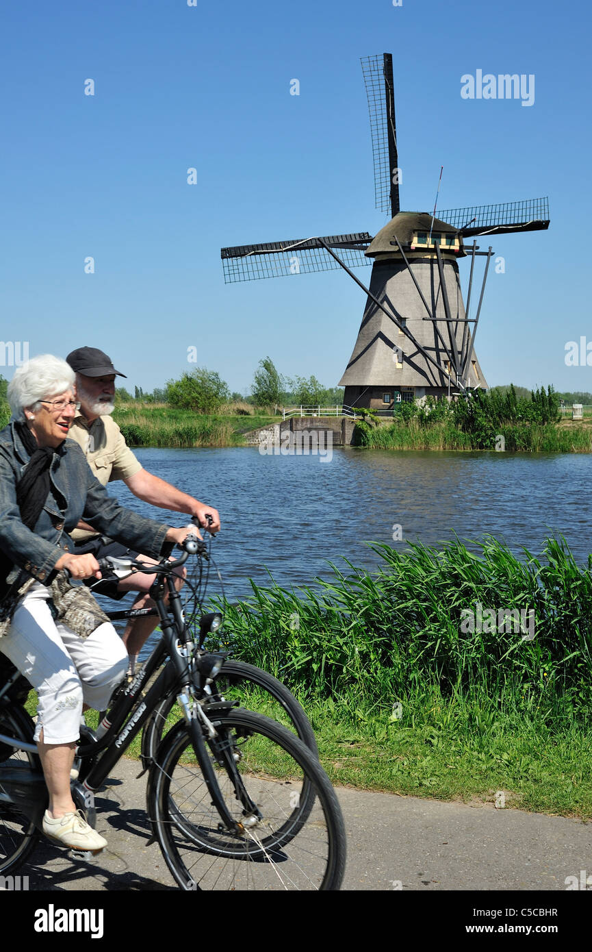 Elderly couple cycling and thatched windmill at Kinderdijk, a UNESCO World Heritage Site at South Holland, the Netherlands - Stock Image