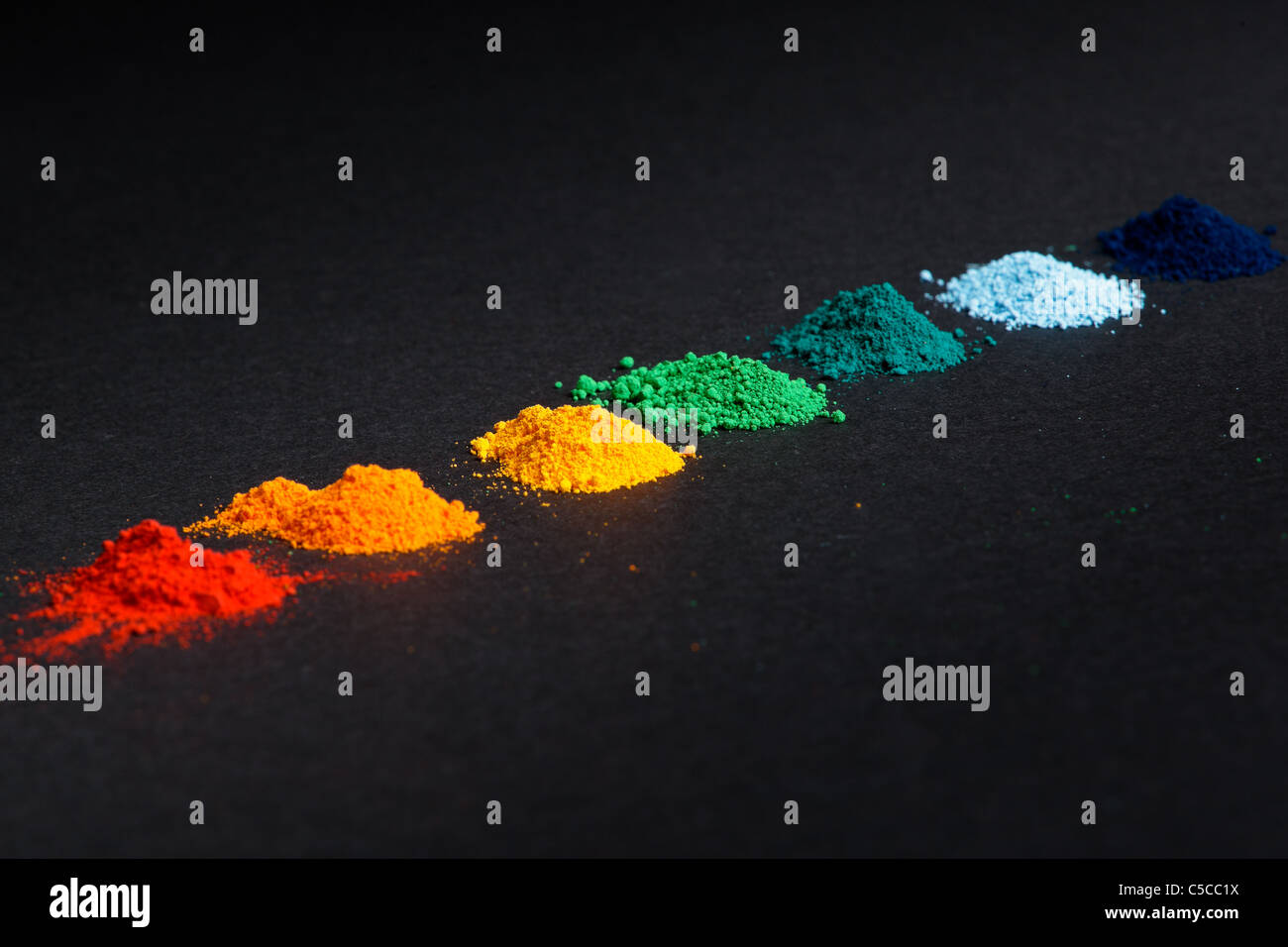 Piles of powdered food colouring in a row - Stock Image