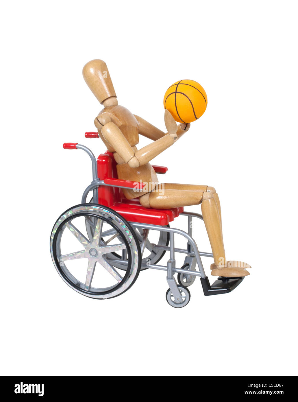 Wooden model in wheelchair shooting basketball - Stock Image