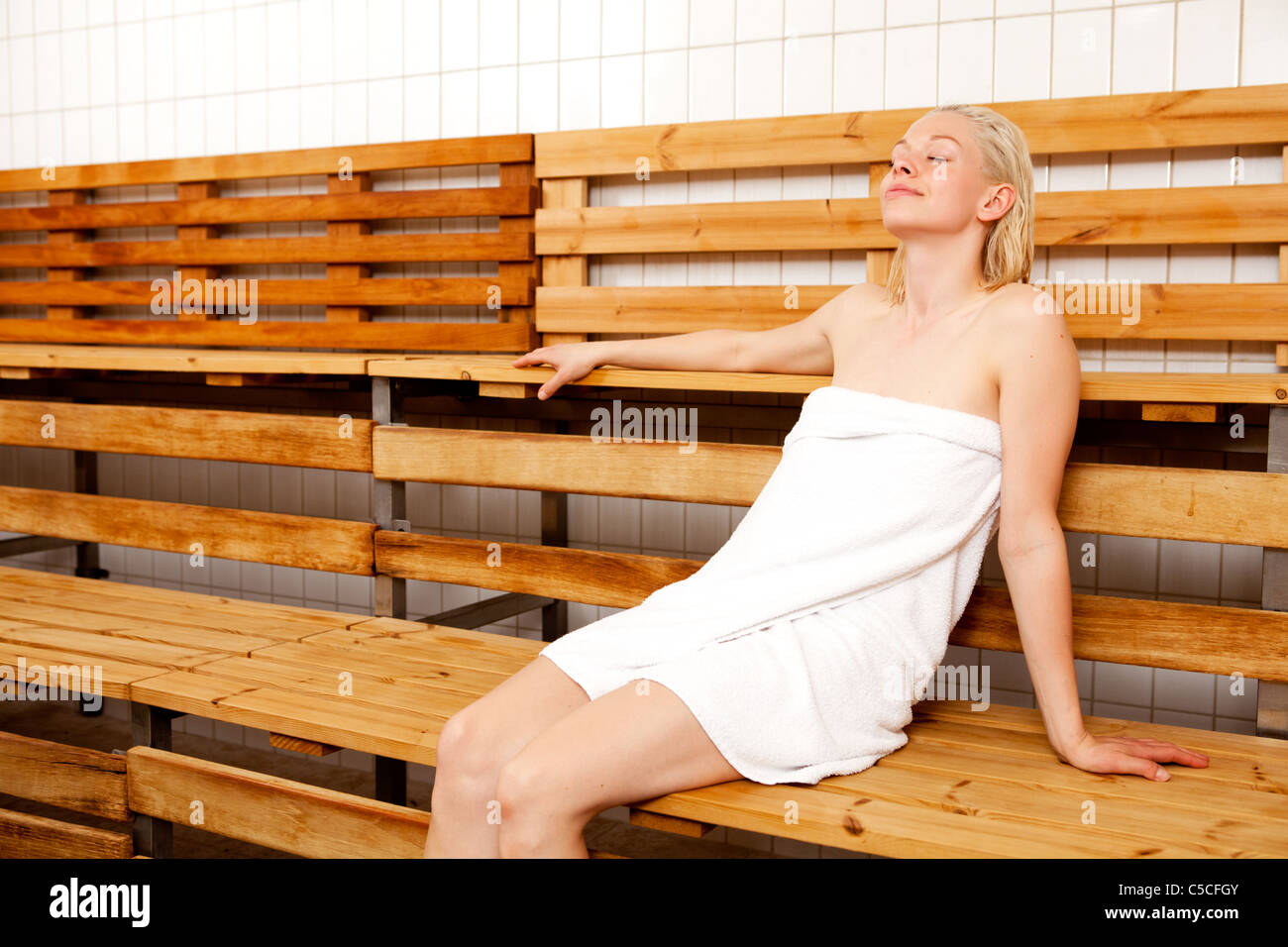 A woman sitting with eyes closed in a spa sauna - Stock Image