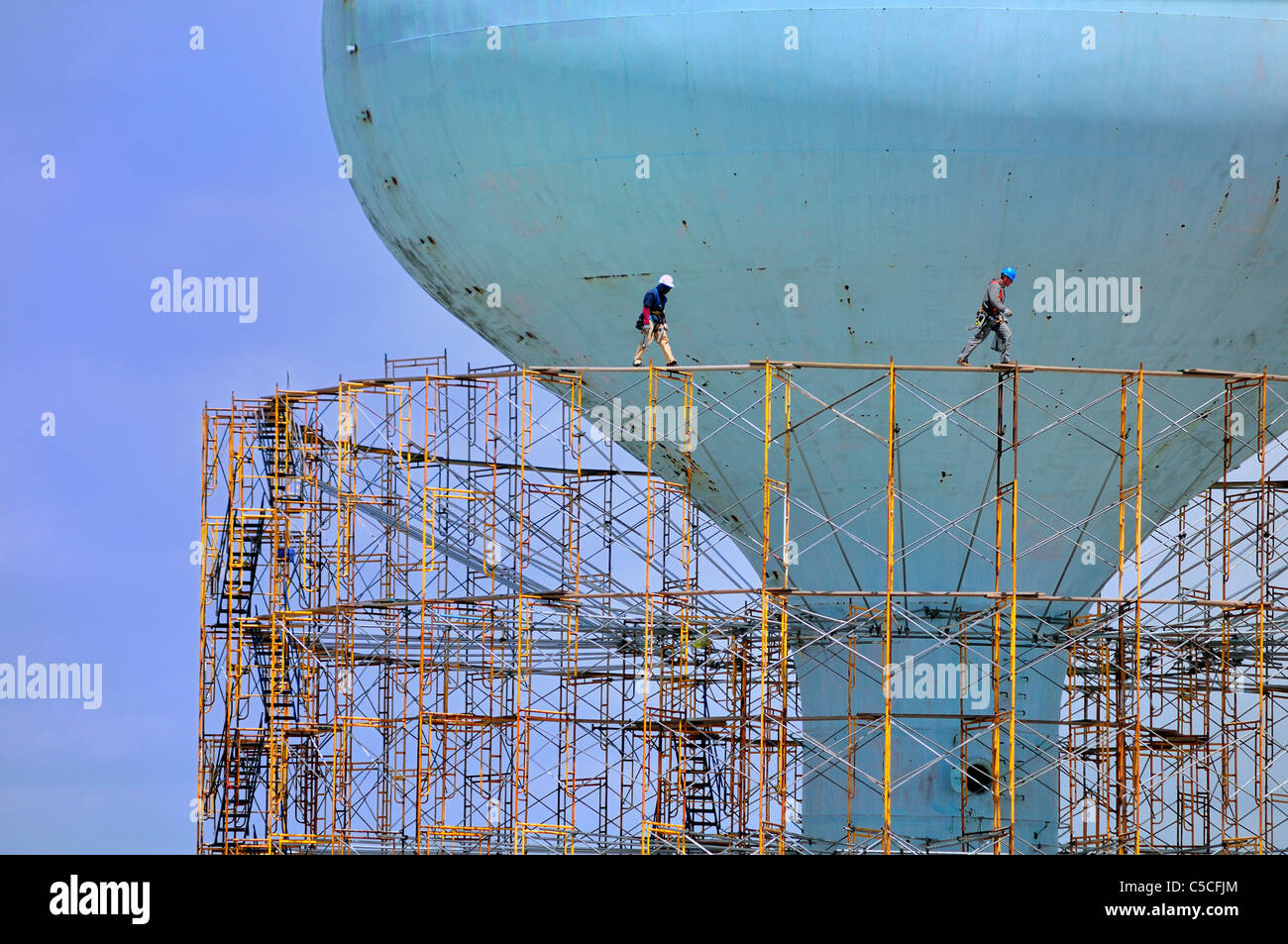 Workman walk along a catwalk atop scaffolding surrounding the water tower on 14th St. in Brigantine Beach - Stock Image