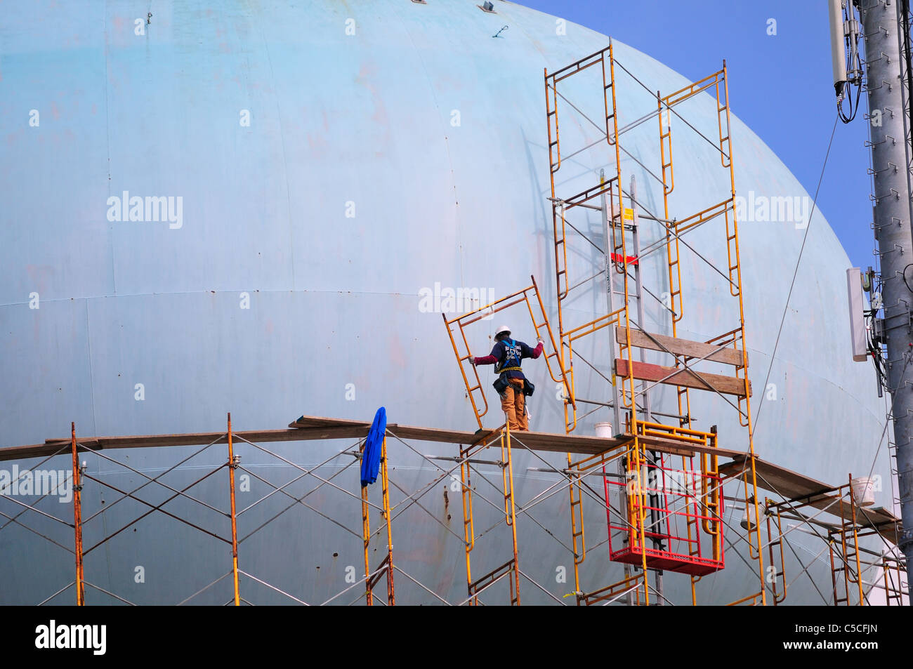 A workman carries a metal section of the scaffold while walking along a catwalk on a water tower in Brigantine Beach - Stock Image