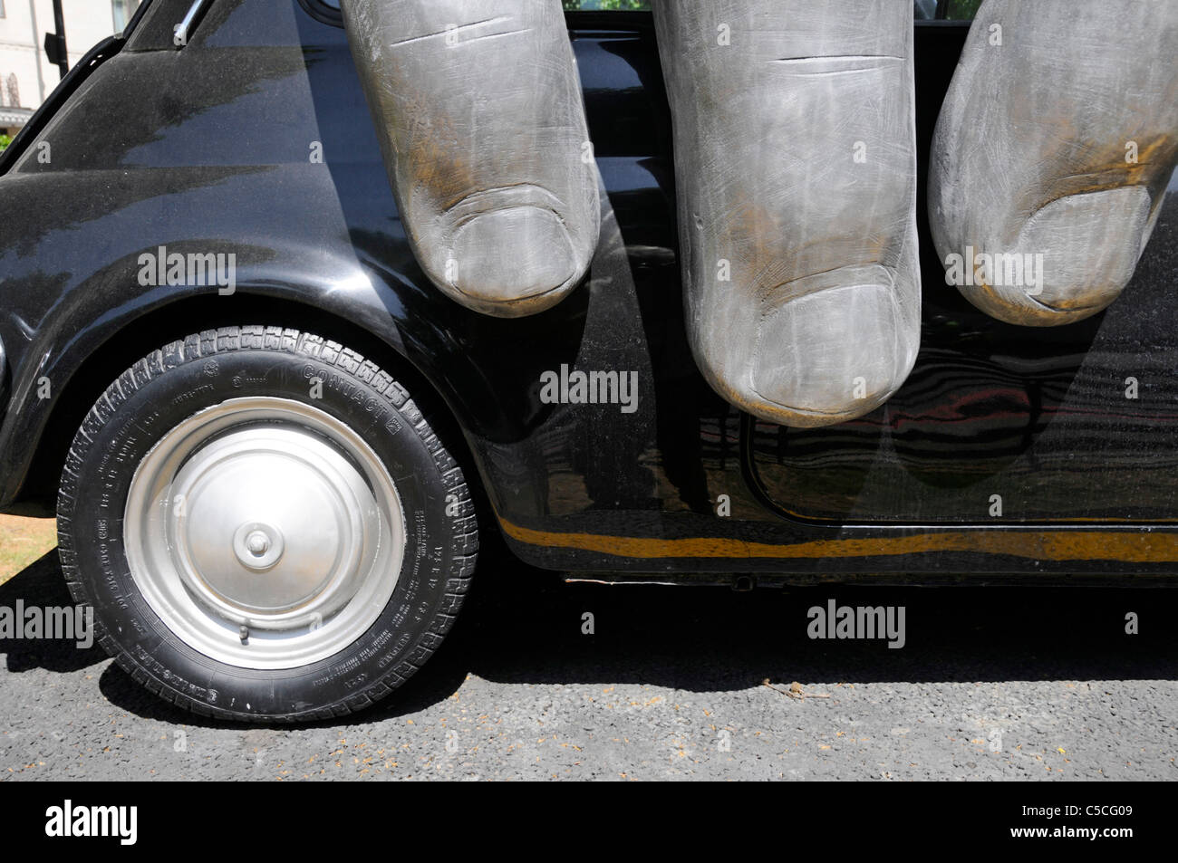 """Close up fingers on Fiat car part of modern art sculpture """"Vroom Vroom"""" by Italian artist Lorenzo Quinn middle of Stock Photo"""